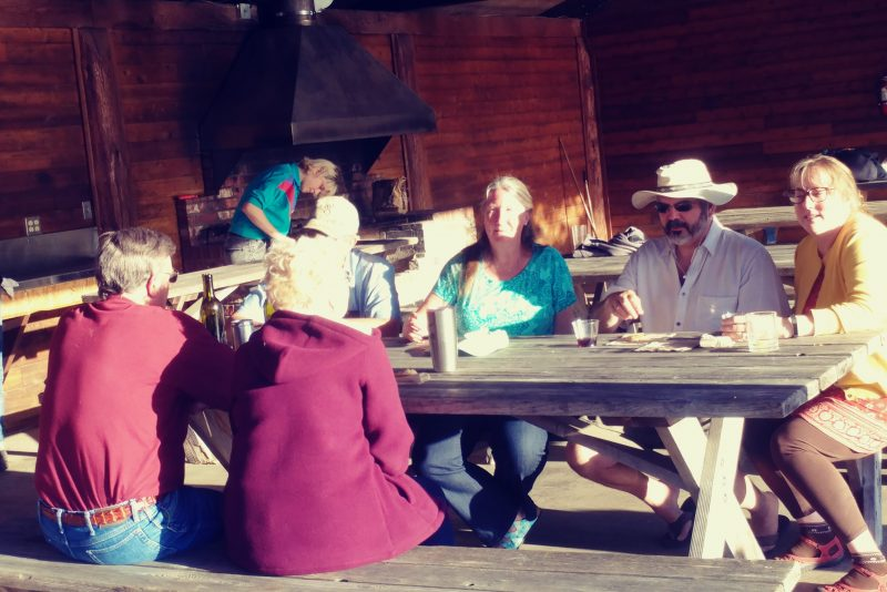 family and friends sitting at picnic table